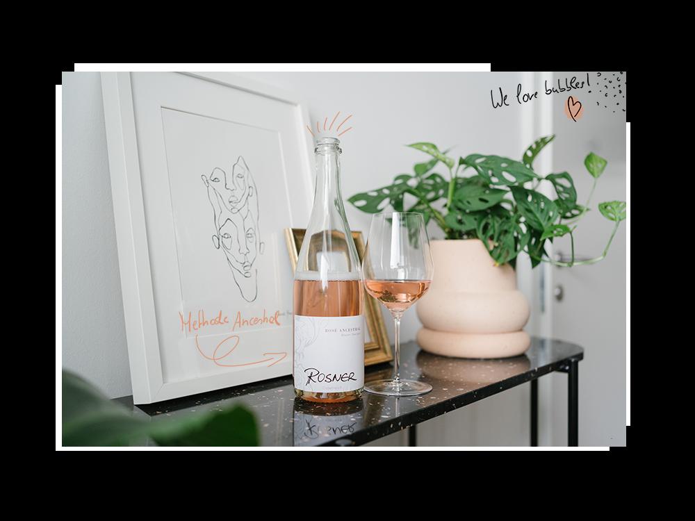 Eine Flasche Rosé Ancestral von Weingut Stefan Rosner und daneben ein gefülltes Glas.