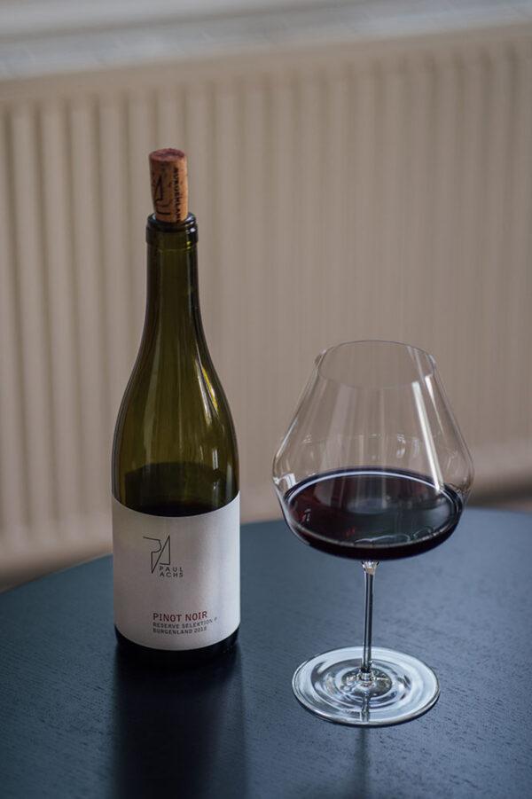 Eine Flasche Pinot Noir vom Weingut Paul Achs und ein Glas von Mark Thomas gefüllt mit dem Pinot.